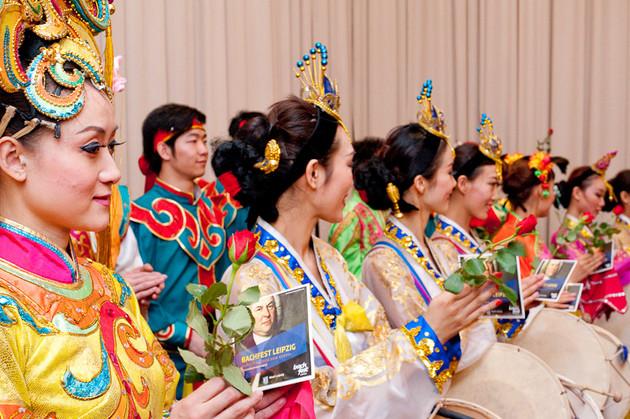 Porträtaufnahme der Tänzerinnen mit traditionellen chinesischen Seidengewändern und Kopfschmuck, die Tänzerinnen halten eine CD mit dem Konterfei Bachs und eine Rose in der Hand