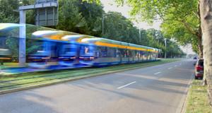 Straßenbahn auf separatem Gleisbett neben einer Straße