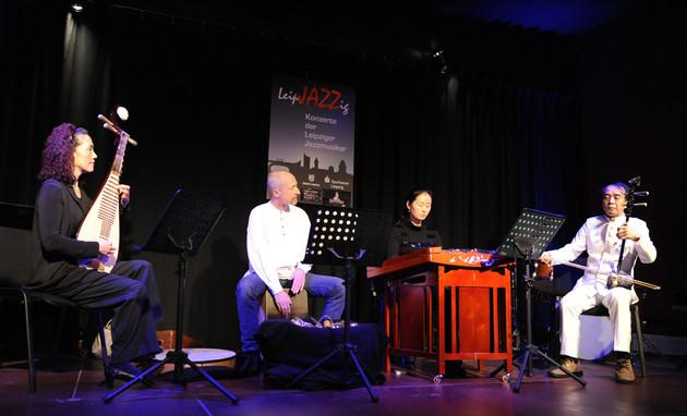 Vier Musiker mit chinesischen Instrumenten musizieren im Scheinwerferlicht auf einer Bühne