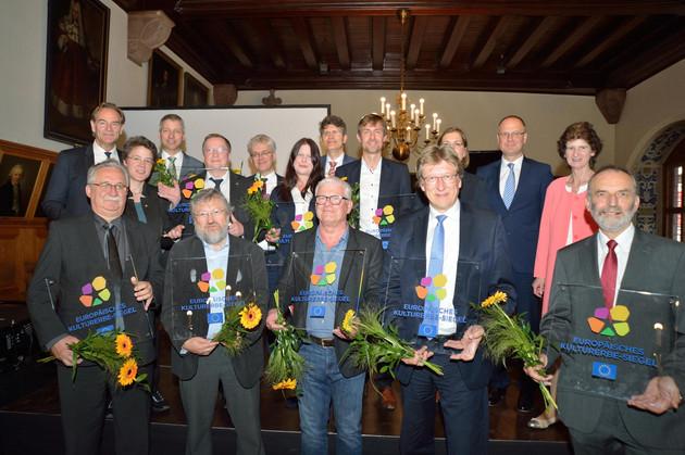 """Eine Gruppe von Menschen erhält eine Auszeichnung. Sie halten Glasplatten in den Händen. Auf den Platten steht: """"Europäisches Kulturerbesiegel""""."""