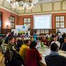 Circa 60 Menschen diskutieren an kleinen Tischen zu je 10 bis 15 Menschen.
