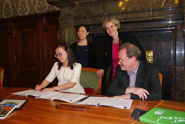 """Eine Vertreterin des Ensembles """"Kleine Rote Blüten"""" aus Nanjing unterzeichnet eine Kooperationsvereinbarung mit dem Leiter der Leipziger Musikschule """"Johann Sebastian Bach"""", Direktor Frank-Thomas Mitschke."""