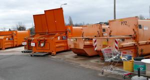 Große, orangefarbene Container stehen auf einem Asphaltplatz