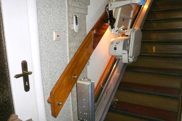 Bild wird vergrößert: Ein Treppenlift ist an einer Treppe montiert.