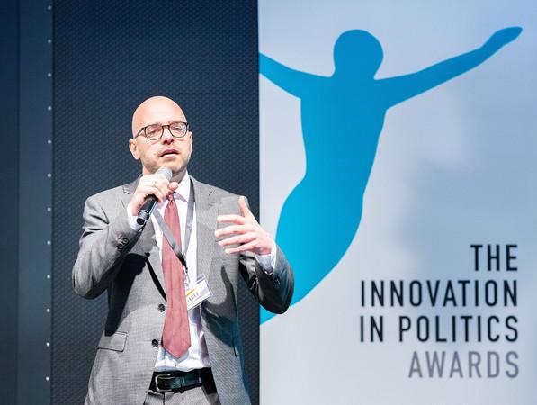 Ein Mann steht vor einem Roll up auf dem The Innovation in Politics Award steht und spricht in ein Mikrofon.