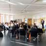 Blick ins Plenum: circa 60 Menschen sitzen in einem Halbkreis, vorne steht ein Redner