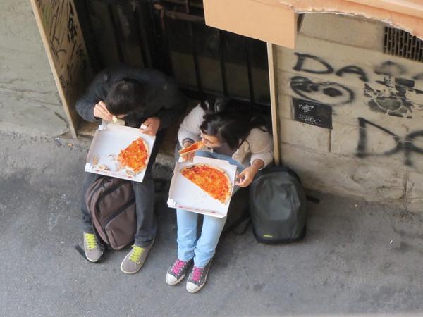 Blick vom Balkon auf zwei in einer Gasse sitzende Personen, die Pizza essen