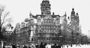 Alte Schwarz-Weiß-Fotografie des Leipziger Neuen Rathauses im Winter 1920. Es liegt Schnee, vor dem Rathaus fahren Pferdekutschen.