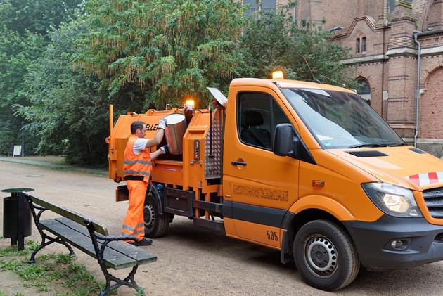 Mitarbeiter der Stadtreinigung leer Mülleimer im Park in kleines Sammelfahrzeug