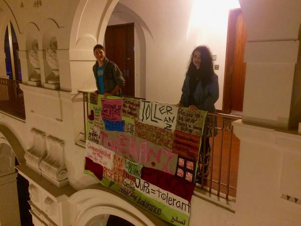 Eine Jugendparlamentarierin und ein Jugendparlamentarier mit einer Flagge auf der in verschiedenen Formen und Farben Toleranz steht.