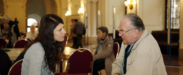 Eine junge Frau und ein älterer Herr sitzen an einem Tisch und diskutieren miteinander.