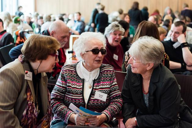 Drei ältere Frauen sitzen auf Stühlen und unterhalten sich. Die mittlere trägt eine Sonnenbrille. Im Hintergrund sieht man, dass der ganze Saal voll mit Menschen ist.