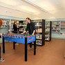 Jugendbereich der Bibliothek Plagwitz mit Einbauregalen in den Wänden, im Vordergrund ein einem Kickertisch, zwei Personen spielen.