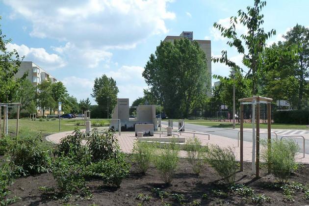 Gestaltete Grünfläche mit Strauchpflanzungen, Bäumen und einer Platzgestaltung mit Bänken
