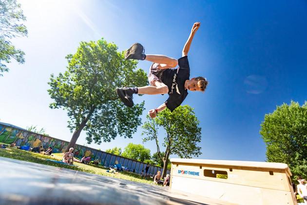 Ein Parkour-Artist springt über einen Kasten.