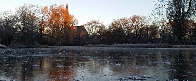 Eisfläche auf einem Teich im Johannapark. Hinter kahlen Bäumen ist eine Kirche sichtbar.