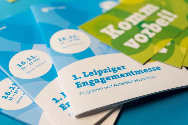 """Bild mit drei Begleitbroschüren zur 1. Leipziger Engagementmesse und der Ankündigungspostkarte zur Messe mit dem Titel """"Komme vorbei""""."""