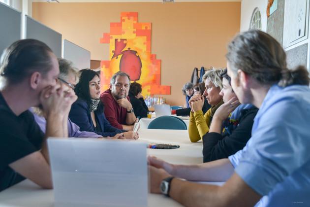 Männer und Frauen verschiedener Altersgruppen sitzen um einen Tisch herum. Darauf: eine beschreibbare Tischdecke und zahlreiche Stifte. Eine junge Frau am Tisch spricht. Der Rest hört zu und betrachtet sie konzentriert.