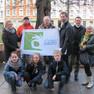 """Eine Gruppe Erwachsene steht im Freien und hält ein kleines Transparent mit der Aufschrift """"Let's clean up europe""""hoch. Davor drei Kinder in der Hocke."""