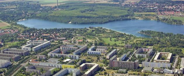 Luftaufnahme der Großsiedlung Grünau mit dem Kulkwitzer See. Im Vordergund sieht man Hochhäsuer, im Hintergrund den Kulkwitzer See