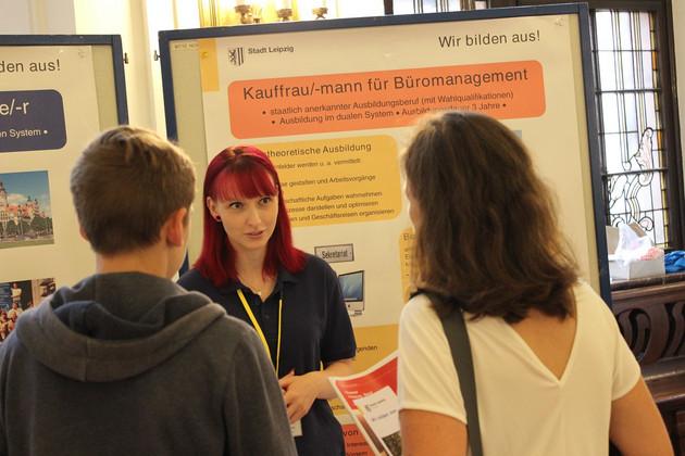 Vor einer Infotafel zum Beruf Kauffrau/-mann für Büromanagement steht eine junge Frau und redet mit zwei Interessierten.