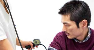 Eine Frau misst einem Mann den Blutdruck.