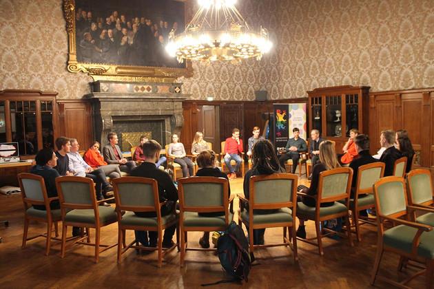 Viele Jugendliche sitzen in einem Stuhlkreis im Festsaal des Neuen Rathauses zusammen und diskutieren