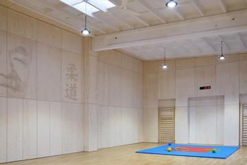 Bild wird vergrößert: Innenraumgestaltung der Judohalle mit Wandgestaltung. Durch Perforation entstehen Schriftzeichen und das Konterfei des Judo-Begründers.
