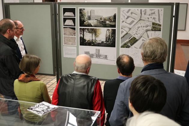 Menschen stehen vor einer Pinnwand und betrachten Pläne.