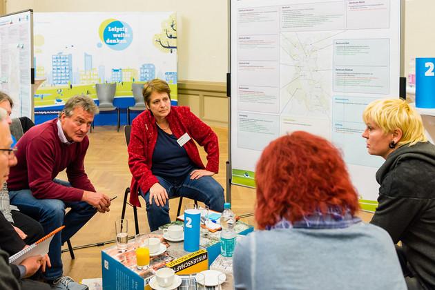 Etwa 5 Menschen sitzen in einer Runde und diskutieren. Im Hintergrund steht eine beschriebene Tafel.