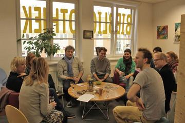 Bild wird vergrößert: Mehrere Männer und Frauen sitzen auf Stühlen um einen kleinen runden Tisch herum, auf dem ein paar Snacks und Getränke stehen.