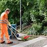 Ein Mitarbeiter der Stadtreinigung kehrt mit Schaufel und Besen Grünschnitt auf