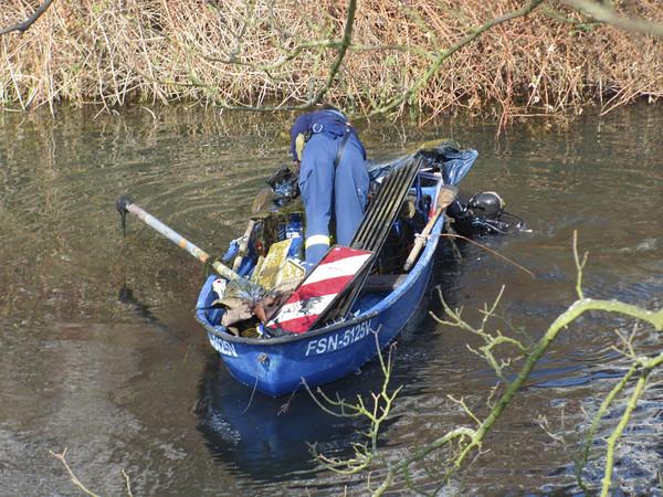 Ein blaues Boot auf einem Kanal. Es ist voller Schrott. In der Mitte steht ein Mann in blauer Arbeitskleidung, der sich gerade zum Wasser hinunterbeugt.