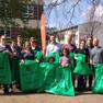 Eine Gruppe Erwachsener und zwei Kinder mit großen grünen Müllsäcken in der Hand.