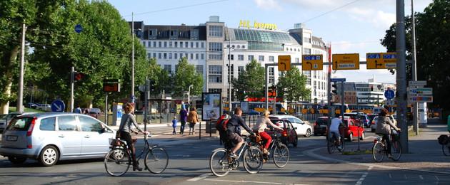 Fahrradfahrer und Autofahrer auf dem Leipziger Innenstadtring. Im Hintergrund fährt eine Straßenbahn.