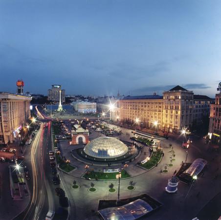 Maydan-Platz mit Glaskuppelhalle und kleinen Bäumen umfasst von Häusern im Stadtzentrum Kiews in der Abenddämmerung