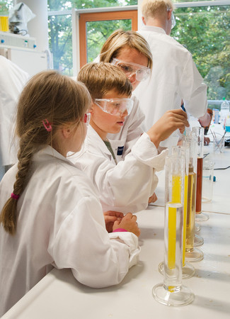 Zwei Kinder und eine Frau tragen Laborkittel und Schutzbrillen. Sie experimentieren mit verschiedenen Flüssigkeiten in Reagenzgläsern.