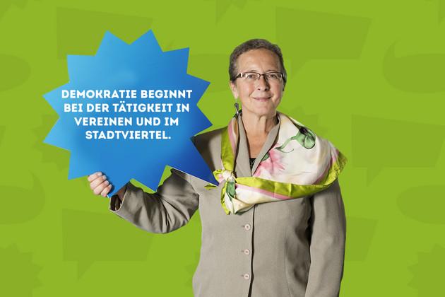 """Die Stadträtin Dr. Sabine Heymann hält ein Schild mit dem Statement """"Demokratie beginnt bei der Tätigkeit in Vereinen und im Stadtviertel.""""."""