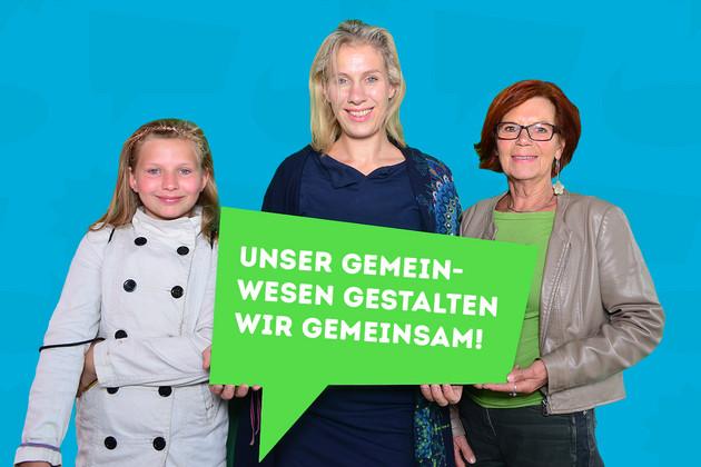 """Frau Krefft und ihre Familie haben sich mit dem Statement """"Unser Gemeinwesen gestalten wir gemeinsam!"""" auf einer grünen Sprechblase fotografieren lassen."""