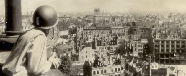 Ein Mann mit Helm steht am Geländer und schaut von einem Turm auf die zerstörte Stadt. Vielen Häusern fehlt das Dach.
