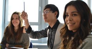 Drei Studenten in einem Zimmer. Ein Student meldet sich mit einem Stift in der Hand.