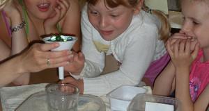 Kinder beim Experimentieren mit einem Glas und Murmeln in einem Trichter.