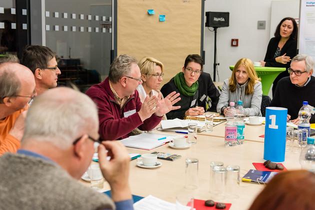 Etwa 15 Menschen sitzen an einem Tisch und diskutieren