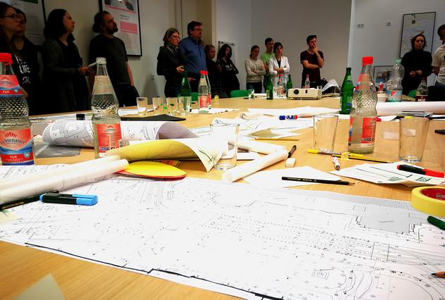 Tisch mit Arbeitsmaterialien und Studenten