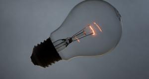 Eine Glühbirne liegt auf weißem Untergrund und leuchtet leicht.