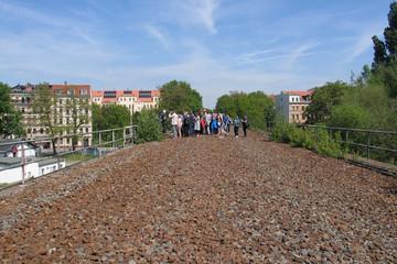 Bild wird vergrößert: Eine Gruppe Menschen steht einer ehemaligen Bahnbrücke, die noch mit Steinen des Gleisbetts gefüllt ist.