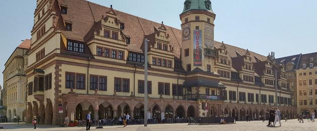 Das Alte Rathaus am Markt mit einer schmuckvollen Fassade und einem Rathausturm mit großer Uhr.