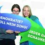 """Zwei Frauen zur Statementkampagne zum Jahr der Demokratie mit grüner Sprechblase auf der steht """"Jeder darf schaukeln."""" und mit blauer Sprechblase auf der steht """"Demokratie? Voll mein Ding."""""""