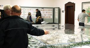 Menschen schauen sich Stadtpläne und Stadtmodelle an