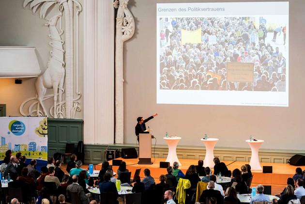 Zuschauer blcken auf eine Bühne, dort zeigt der Referent auf die Leinwand.